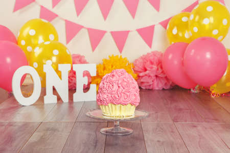 Festive background decoration for birthday celebration with pink girl cupcake or cake on glass stand, letters saying one and pink red yellow balloons in studio. Cake-smash first year concept.