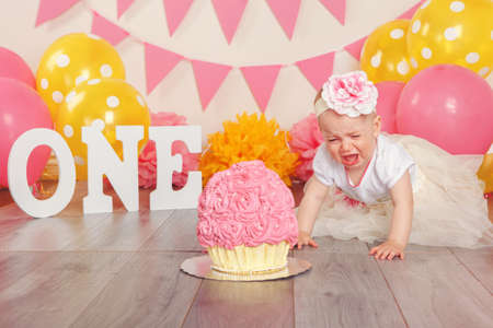 Portrait of crying upset Caucasian baby girl in tutu tulle skirt celebrating her first birthday. Cake smash concept. Child kid sitting on floor in studio with pink flags and balloons  Stock fotó