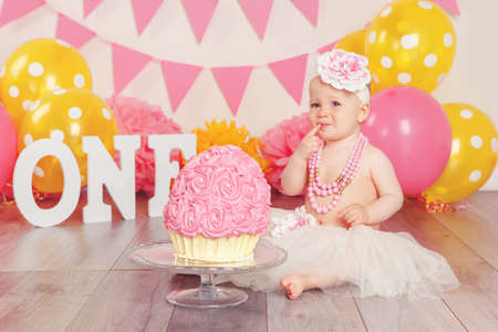 Portrait of cute adorable Caucasian baby girl in tutu tulle skirt celebrating her first birthday. Cake smash concept. Child kid sitting on floor in studio with pink flags and balloons, eating dessert  Stock fotó