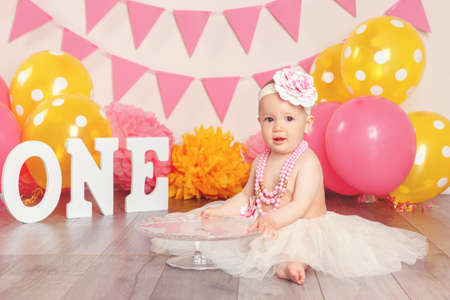 Portrait of cute adorable Caucasian baby girl in tutu tulle skirt celebrating her first birthday. Child kid sitting on floor in studio with pink flags and balloons holding cake stand  Stock Photo