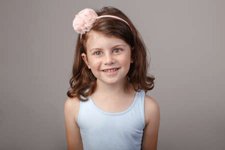 Closeup portrait of cute adorable white brunette Caucasian preschool girl making faces in front of camera. Child smiling laughing posing in studio on plain light background. Kid expressing emotions Stock Photo
