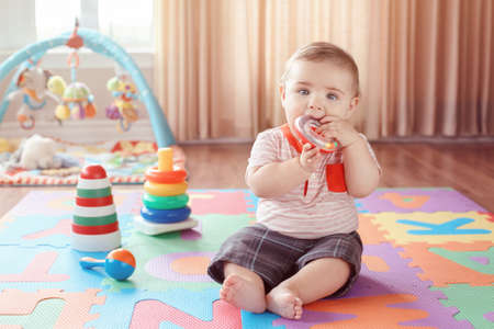Portrait of cute adorable blond Caucasian smiling child boy with blue eyes sitting on floor in kids children room chewing ring. Little baby playing with teething toys. Early education development concept.
