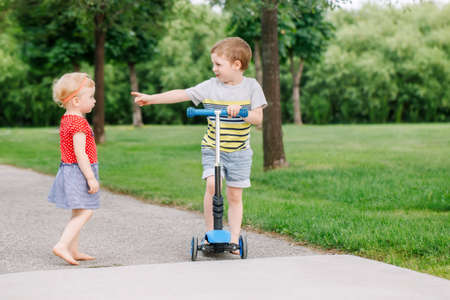 Two little Caucasian preschool children fighting in park outside. Boy and girl can not share one scooter. Older sibling brother not giving his toy to younger sister. Communication problems.