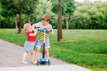 Twee kleine blanke kleuters vechten elkaar raken. Jongen en meisje kunnen geen scooter delen. Oudere broer of zus geeft zijn speeltje niet aan jongere zus. Communicatieproblemen.