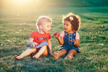 Group portrait of white Caucasian and latin hispanic girls children sitting together sharing apple. Two babies eating fruits outside in park on summer day. Best friends forever. Healthy childhood. Фото со стока