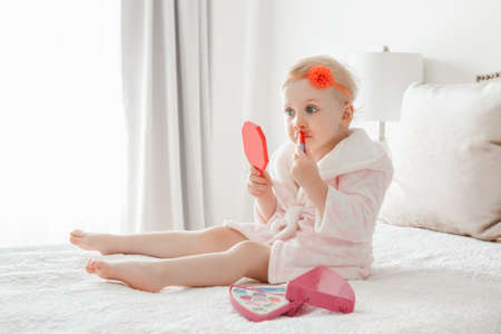 Cute asorable funny Caucasian blonde baby girl 2 years old in bathrobe doing applying makeup, looking into mirror and sitting on her bed in bedroom at home. Happy childhood concept.