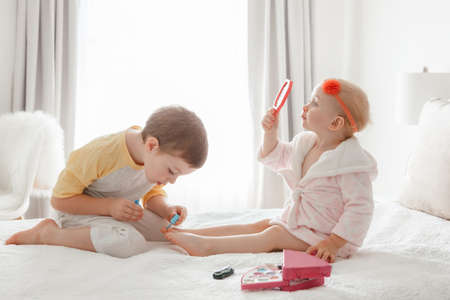 Adorable Caucasian boy and girl siblings playing together painting nails sitting on bed at home. Older brother doing manicure pedicure for his little younger sister. Friends toddlers using cosmetics. 版權商用圖片
