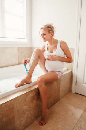 Problems and difficulties during pregnancy. Portrait of pregnant blonde Caucasian woman shaving legs in bathroom. Expecting mom doing cosmetological procedures in the morning.