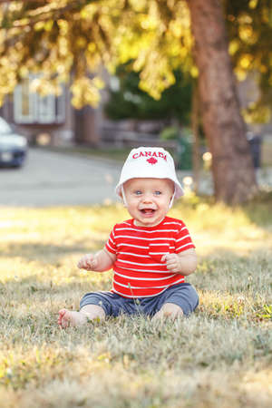 Portrait of little white Caucasian baby boy wearing Canadian hat with maple leaf. Child sitting on grass in park on July summer day. Toddler celebrating national Canada day Stock Photo