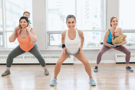 Group of three young women with children doing workout in gym class with instructor to loose baby weight. Child-friendly fitness for mothers with kids toddlers. Lifestyle concept of parent activity