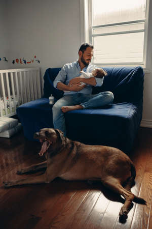 Portrait of middle age Caucasian father with newborn baby. Dog pet laying on floor. Man parent holding child in hands. Authentic lifestyle documenatry moment. Single dad family life. Foto de archivo - 116427340