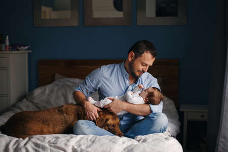 Portrait of middle age Caucasian father with newborn baby. Dog pet laying on bed. Man parent holding child in hands. Authentic lifestyle documenatry moment. Single dad family life. Foto de archivo - 116427345