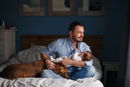Portrait of middle age Caucasian father with newborn baby. Dog pet laying on bed. Man parent holding child in hands. Authentic lifestyle documenatry moment. Single dad family life.