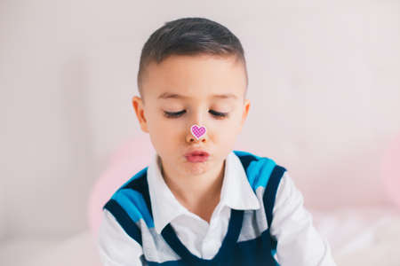 Funny hilarious authentic white Caucasian cute adorable child boy looking at her nose with heart sticker on it. Valentine day holiday concept.