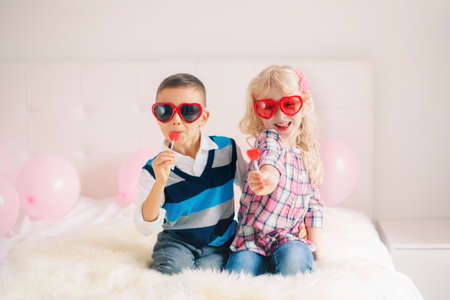 Group portrait of two happy white Caucasian cute adorable funny children eating heart shaped lollipops. Boy and girl celebrating Valentine Day. Love, friendship and fun. Best friends forever.
