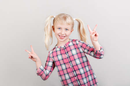 Closeup portrait of cute adorable white blonde Caucasian preschool girl smiling in front of camera in studio. Child posing showing victory sign on plain light background. Kid expressing emotions Stok Fotoğraf