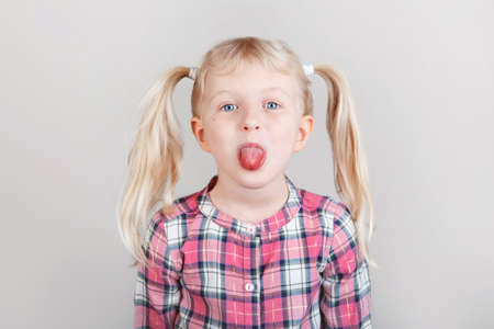 Closeup portrait of funny blonde Caucasian preschool girl making faces in front of camera. Child showing tongue on plain light background. Kid expressing emotions. April fools day concept
