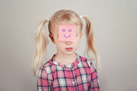 Closeup portrait of sad unhappy white blonde Caucasian preschool girl with funny sticky note paper on her face. Kid expressing emotions. Concept of difficulties, problems of childhood.
