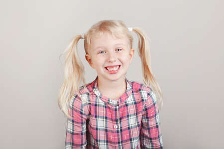 Closeup portrait of cute adorable white blonde Caucasian preschool girl smiling in front of camera in studio. Child laughing posing on plain light background. Kid expressing emotions