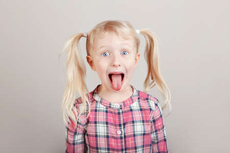 Closeup portrait of funny blonde Caucasian preschool girl making faces in front of camera. Child showing tongue on plain light background. Kid expressing emotions. April fool's day concept Stockfoto