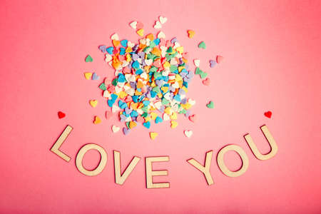 Happy Valentine Day. Beautiful card with pile of colorful hearts candies on pink coral background. Concept of February holiday. Wooden words letters saying love you.