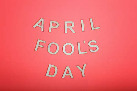 Happy 1 April Fool's day. Beautiful holiday card with wooden letters on pink living coral color background.