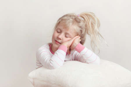 Healthy sleep concept. Cute blonde Caucasian girl child in pink pajamas with closed eyes pretending sleeping in studio on white soft fluffy pillow.