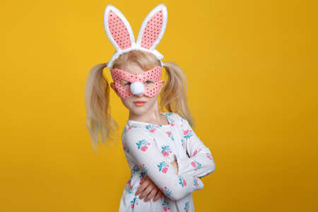 Cute grumpy Caucasian blonde girl in white dress wearing pink Easter bunny ears and mask posing in studio on yellow background with arms crossed on her chest Standard-Bild - 118488989