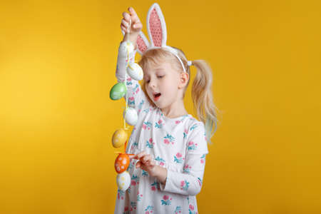 Cute adorable Caucasian blonde girl in white dress with pink  Easter bunny ears playing with eggs in studio on yellow background. Funny kid child celebrating traditional Christian holiday