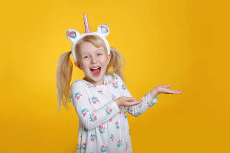 Cute adorable smiling Caucasian blonde girl in white dress wearing unicorn headband horn and ears in studio on yellow background. Funny kid child expressing emotion and showing pointing