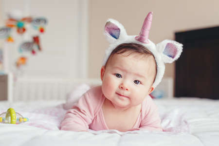 Portrait of cute adorable Asian mixed race smiling baby girl four months old lying on tummy on bed in bedroom wearing unicorn headband horn and ears looking in camera.