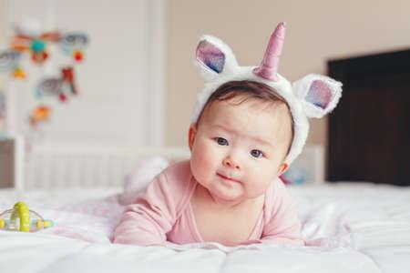 Ritratto di carino adorabile razza mista asiatica sorridente bambina di quattro mesi sdraiato sulla pancia sul letto in camera da letto indossando fascia unicorno corno e orecchie guardando a porte chiuse.
