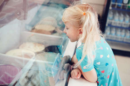 Caucasian funny blonde child girl looking at ice cream in shop window trying to choose one. Kid with puzzled emotional face expression. Candid childhood lifestyle. Tasty frozen summer food.