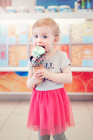 Cute adorable Caucasian toddler girl child with blue eyes holding ice cream in large waffle cone with sprinkles. Baby licking frozen food. Happy childhood lifestyle. Tasty summer dessert