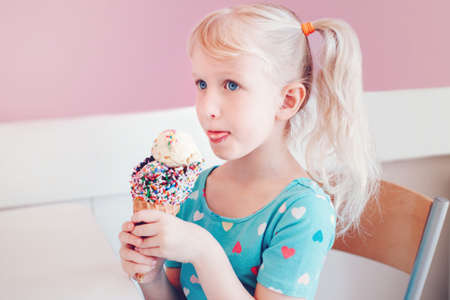 Cute adorable funny Caucasian blonde preschool girl child with blue eyes and pigtails eating licking ice cream in large waffle cone with sprinkles. Happy childhood lifestyle. Tasty summer food Stock Photo