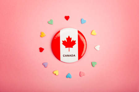 Happy Canada Day greeting card with Canadian flag in centre middle and many colorful candies hearts around it on living coral pink background. Multiculturalism national values concept.