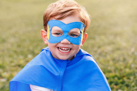 Cute smiling preschool Caucasian child playing superhero in blue costume. Boy kid wearing mask and cape having fun outdoors in park. Happy active childhood. Power and protection concept.