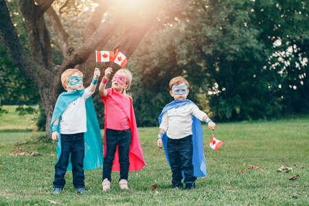 Niños caucásicos en superhéroes cotumes y máscaras sosteniendo ondeando la bandera canadiense. Niños, niñas celebrando el día de fiesta nacional de Canadá en el parque de verano al aire libre. Concepto de fuerza, potencia y protección. Foto de archivo