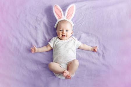 Cute adorable white Caucasian baby girl wearing pink Easter bunny ears lying on pink purple bed in bedroom. Funny kid infant celebrating traditional Christian holiday. View from top above