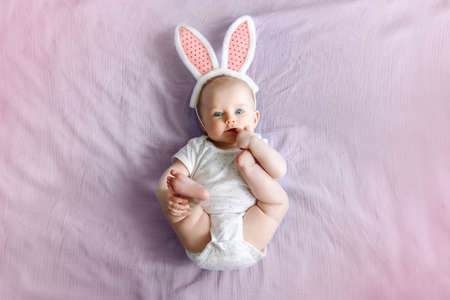 Cute adorable white Caucasian baby girl wearing pink Easter bunny ears lying on pink purple bed in bedroom. Funny kid infant celebrating traditional Christian holiday. View from top above Archivio Fotografico