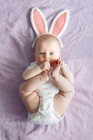 Carino adorabile bianco caucasico bambina indossa rosa coniglietto di Pasqua orecchie sdraiato sul letto viola rosa in camera da letto. Bambino divertente che celebra la festa cristiana tradizionale. Vista dall'alto dall'alto