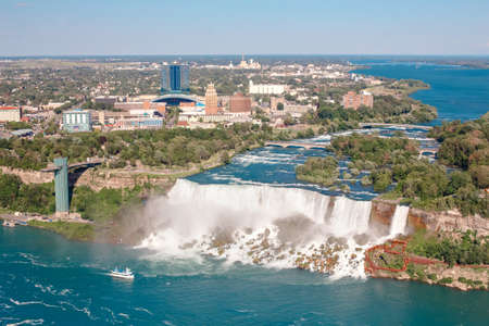 Aerial top landscape view of Niagara Falls between United States of America and Canada. View on America state New York from Canadian waterfall. Water tour boat at famous tourist landmark