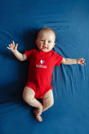 White Caucasian smiling baby boy girl with blue eyes lying on bed at home on Canada Day. Newborn infant child in red onesie romper celebrating national holiday July 1. View from top above Фото со стока