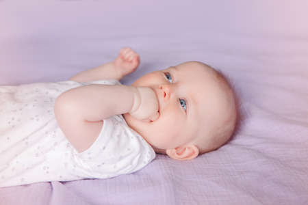Closeup portrait of cute adorable white Caucasian infant child girl boy with blue eyes lying on bed licking sucking fingers fist. Baby teething. Happy childhood lifestyle and newborn development. Archivio Fotografico - 121032123