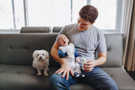 Young Caucasian father feeding newborn baby with milk. Male man parent with dog and yawning child on his hands. Authentic lifestyle funny candid moment. Single dad family life concept Foto de archivo - 122567685