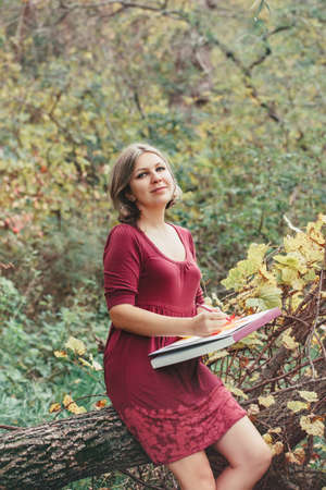 Portrait of smiling Caucasian woman artist drawing in open plein air in park outside with pencils on paper in album. Lifestyle activity hobby. Freelancer illustrator at remote distance work place