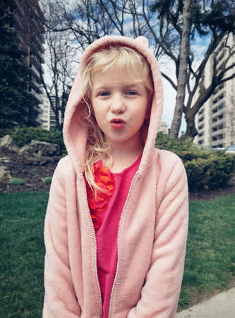 Funny face. Portrait of cute adorable preschool blonde Caucasian in red t-short and pink hoodie. Girl child making funny silly faces with duck lips. Kid having fun in park outside in city.