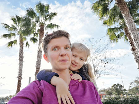 Portrait of happy white Caucasian mother and daughter girl making selfie on phone camera outside. Mom and child hugging in Florida park among tropical palm trees. Candid authentic lifestyle.