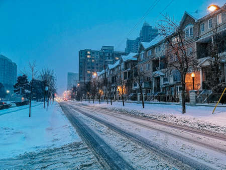 Scenic view landscape of outdoor winter city town Toronto at late evening night. Buildings, houses, trees, roads and streets covered with snow. Heavy snowstorm natural disaster cataclysm. Stock Photo