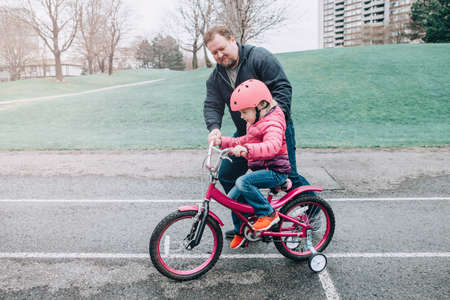 Caucasian father dad training helping girl daughter to ride bicycle. Preschooler child kid in pink helmet with bike on backyard road outside on spring day. Seasonal child family outdoor activity